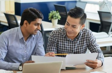 Cheerful multi-ethnic business people discussing documents at meeting in office
